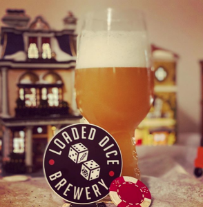 A glass of Loaded Dice Brewery beer with a logo sticker and a poker chip.